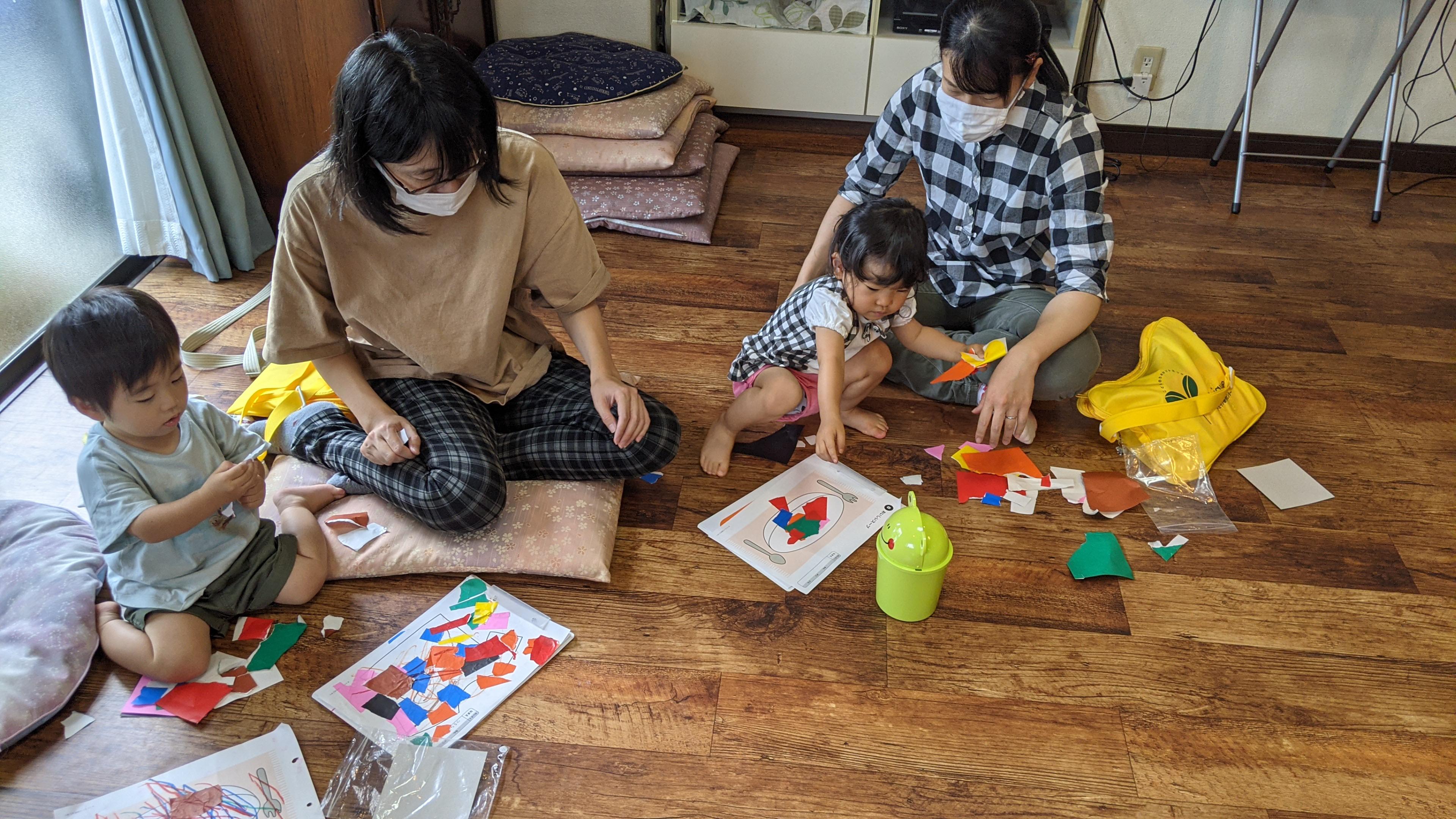 リトミックで折り紙をちぎって紙に貼る一歳児